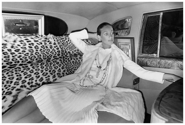 marisa-berenson-seated-in-the-back-of-a-car-with-leopard-seats-wearing-white-chanel-ensemble-with-a-pleated-dress-white-fur-coat-and-chain-necklaces-photo-arnaud-de-rosnay-1968
