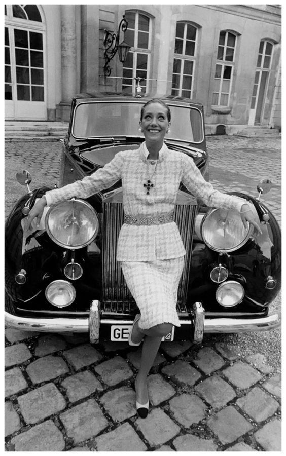 marisa-berenson-leaning-on-grill-of-a-rolls-royce-wearing-a-chanel-skirt-suit-with-crucifix-medallion-on-chain-and-belt-photo-arnaud-de-rosnay-1969