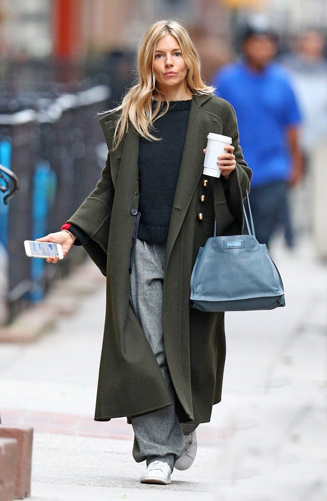"""Una sempre elegante Sienna Miller, passeggia per New York con un outfit casual impreziosito da una cerulea Prada"""" Etiquette"""". Da notarela versione in pelle dell'etichetta sulla borsa, finora riservata solamente ai capi dall'abbigliamento."""